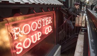 A costumer takes an order to go from the Rooster Soup Co., the newest member of the CookNSolo restaurant group, in Philadelphia, Monday, Jan. 23, 2017. The CookNSolo restaurateurs have found a valuable use for their discarded chicken backs: making soup for charity. All proceeds after expenses will benefit Broad Street Ministry, a local nonprofit serving the hungry and homeless. (AP Photo/Matt Rourke)