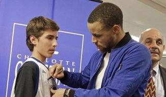 """Golden State Warrior's Stephen Curry signs an autograph after a news conference at his former high school in Charlotte, N.C., Tuesday, Jan. 24, 2017. Curry will be honored during his return home to Charlotte. His high school will be retiring his number while Davidson College will honor him by renaming a section of their arena """"Section 30."""" (AP Photo/Chuck Burton)"""