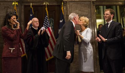 South Carolina Governor Henry McMaster kisses his wife, Peggy, after being sworn in as governor during a ceremonial swearing in at the Statehouse Tuesday Jan. 24, 2017, in Columbia, S.C. At far left is former governor and current ambassador to the United Nations Nikki Haley. Haley resigned as governor to be ambassador to the United Nations. At far right is McMaster's son Henry McMaster, Jr. (AP Photo/Mic Smith)