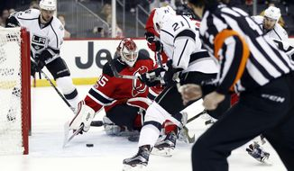 A shot by Los Angeles Kings defenseman Alec Martinez (27) enters the net of New Jersey Devils goalie Cory Schneider (35) during the first period of an NHL hockey game, Tuesday, Jan. 24, 2017, in Newark, N.J. (AP Photo/Julio Cortez)