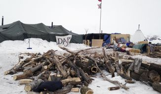 Firewood is stacked up at a protest encampment along the route of the Dakota Access oil pipeline near Cannon Ball, N.D. on Tuesday, Jan. 24, 2017. President Donald Trump on Tuesday issued an executive action to advance construction of the pipeline, which opponents believe threatens drinking water and cultural sites. The pipeline developer disputes that. (AP Photo/James MacPherson)