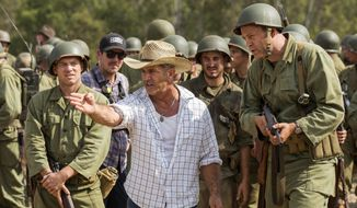 "This image released by Summit shows director Mel Gibson, center, and actor Vince Vaughn on the set of the film, ""Hacksaw Ridge."" Gibson was nominated for an Oscar for best directing  on Tuesday, Jan. 24, 2017, for his work on the film. The 89th Academy Awards will take place on Feb. 26. (Summit via AP)"