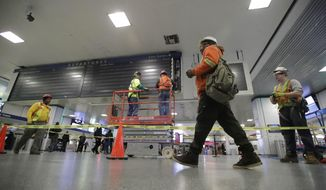 Workers replace the train status board at Penn Station, Monday, Jan. 23, 2017, in New York. The project is scheduled to be completed over the weekend. (AP Photo/Frank Franklin II)