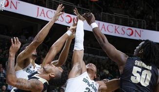 Michigan State's Miles Bridges (22) and Kenny Goins, left rear, and Purdue's Caleb Swanigan (50) and Vincent Edwards, left, vie for a rebound during the first half of an NCAA college basketball game, Tuesday, Jan. 24, 2017, in East Lansing, Mich. (AP Photo/Al Goldis)