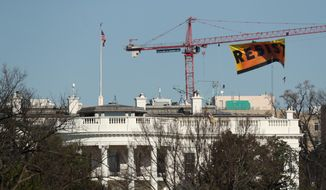 """Greenpeace protesters unfurl a banner that reads """"Resist"""" at the construction site of the former Washington Post building, near the White House in Washington, Wednesday, Jan. 25, 2017, after police say protesters climbed a crane at the site refusing to allow workers to work in the area. (AP Photo/Andrew Harnik)"""