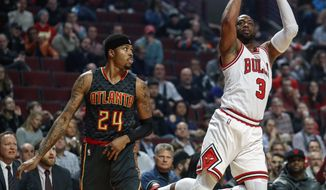 Chicago Bulls guard Dwyane Wade (3) shoots, scores and is fouled on the play by Atlanta Hawks forward Kent Bazemore (24) during the first half of an NBA basketball game, Wednesday, Jan. 25, 2017, in Chicago. (AP Photo/Kamil Krzaczynski)