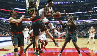 Chicago Bulls forward Jimmy Butler, center, looks to pass the ball against Atlanta Hawks guard Mike Dunleavy (34) and forward Paul Millsap (4) during the first half of an NBA basketball game, Wednesday, Jan. 25, 2017, in Chicago. (AP Photo/Kamil Krzaczynski)