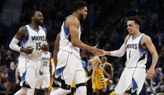 Minnesota Timberwolves teammates Karl-Anthony Towns, center, and Tyus Jones (1) celebrate their lead in the second half of an NBA basketball game Sunday, Jan. 22, 2017, in Minneapolis. The Wolves won 111-108. (AP Photo/Stacy Bengs)