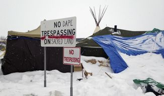 Signs are displayed Wednesday, Jan. 25, 2017, in the bitter weather at an encampment near Cannon Ball, N.D., to protest the Dakota Access pipeline. Some protesters are vowing to stay in the camp despite a Trump administration order that seeks to expedite the pipeline's completion. (AP Photo/James MacPherson)