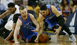 New Orleans Pelicans forward Anthony Davis, left, falls during a battle for the ball against Oklahoma City Thunder forward Domantas Sabonis, center, and center Enes Kanter, right, in the first half of an NBA basketball game in New Orleans, Wednesday, Jan. 25, 2017. (AP Photo/Max Becherer)