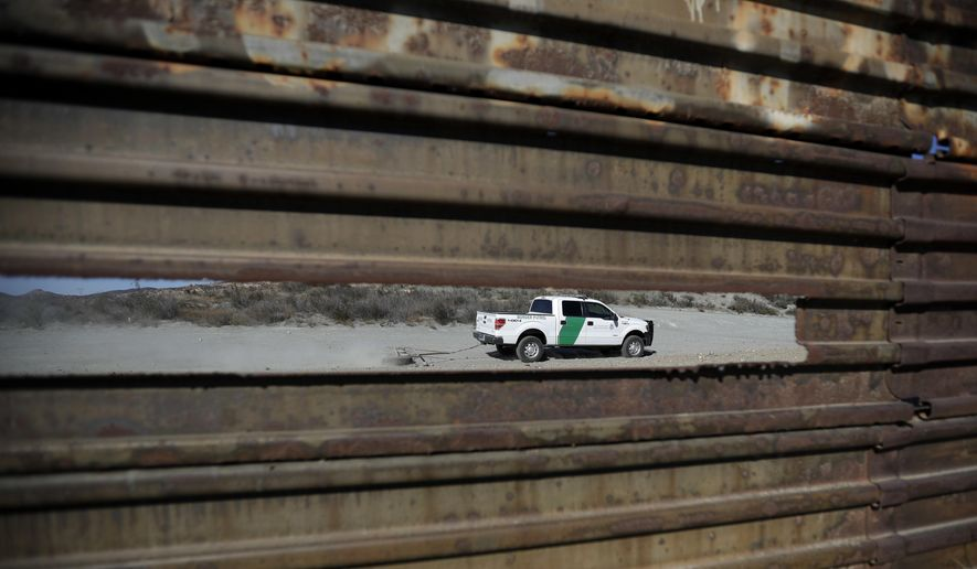 In this Nov. 9, 2016, file photo, a Border Patrol vehicle drives by in Tecate, Calif., seen through a hole in the metal barrier that lines the border in Tecate, Mexico. U.S. President Donald Trump will direct the Homeland Security Department to start building a wall at the Mexican border. (AP Photo/Gregory Bull, file)