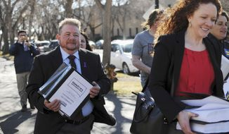 FILE - In this Feb. 23, 2016 file photo, Terri Bruce, left, walks toward the South Dakota state Capitol in Pierre. The bill drew national condemnation and is included in the AP top news stories in South Dakota this year. Two South Dakota lawmakers introduced a bill, introduced Wednesday, Jan. 25, 2017, that would require public school students to use the locker rooms, shower rooms and changing facilities that match their sex at birth. Bruce, a 53-year-old transgender man, fought against the bill last year. (AP Photo/James Nord, File)