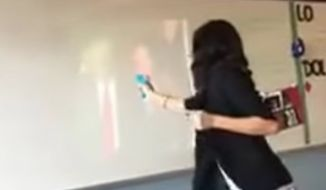 """A Dallas teacher was placed on administrative leave Thursday afternoon after a video showing her firing a water gun at a video of President Trump and yelling """"die"""" was widely shared on social media and conservative news sites."""