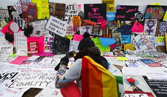 In this Saturday, Jan. 21, 2017 file photo, protesters build a wall of signs outside the White House for the Women's March on Washington during the first full day of Donald Trump's presidency in Washington. Signs from the women's marches around the world are being saved as cultural treasures by museums, libraries and colleges. (AP Photo/John Minchillo, File)