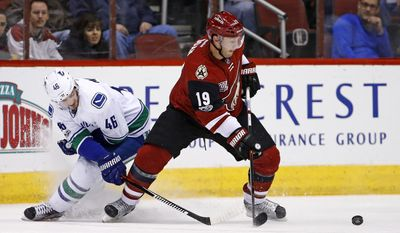 Arizona Coyotes right wing Shane Doan (19) tries to control the puck in front of Vancouver Canucks center Jayson Megna (46) during the first period of an NHL hockey game Thursday, Jan. 26, 2017, in Glendale, Ariz. (AP Photo/Ross D. Franklin)