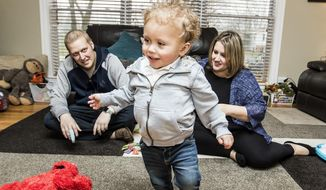 ADVANCE FOR USE SUNDAY, JAN. 29, 2017AND THEREAFTER - In this Jan. 11, 2017 photo, Ryan Wagner and his wife, Ashley Wagner, play with their son, Miles  Wagner, 2, at their home in Woodridge, Ill. In December 2013, Ryan was diagnosed with with stage IV colon cancer a week after finding out that he and his wife were expecting Miles. Then at two months old, Miles was diagnosed with a rare disease that requires him to have both a liver and kidney transplant. He received his donor liver about a year ago and is now getting ready for a kidney transplant. (Sarah Nader/Northwest Herald via AP)