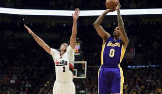 Los Angeles Lakers guard Nick Young hits a three point shot over Portland Trail Blazers guard C.J. McCollum during the first half of an NBA basketball game in Portland, Ore., Wednesday, Jan. 25, 2017. (AP Photo/Steve Dykes)