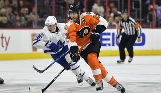 Philadelphia Flyers' Claude Giroux (28) skates with the puck past Toronto Maple Leafs' Mitchell Marner (16) during the second period of an NHL hockey game, Thursday, Jan. 26, 2017, in Philadelphia. (AP Photo/Derik Hamilton)