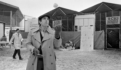 FILE - In this Jan. 20, 1982, file photo, CBS Sportscaster Brent Musburger plays with a snowball outside the Silverdome in Pontiac, Mich., where the XVI Super Bowl will be played. Musburger is calling an end to his broadcast career. Millions of Americans experienced sporting events through his folksy narration, most often when he was the lead voice of CBS Sports during the 1980s. Musburger will call his last game for ESPN on Jan. 31, a college basketball contest pitting Kentucky against Georgia.  (AP Photo/File)