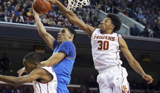 Southern California guard Elijah Stewart (30) gets a hand on the ball as UCLA guard Lonzo Ball (2) shoots during the first half of an NCAA college basketball game in Los Angeles on Wednesday, Jan. 25, 2017. (AP Photo/Reed Saxon)