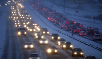 FILE - In this Feb. 1, 2011, file photo, traffic along U.S. Highway 12/14 in Madison, Wis., moves at a crawl as drivers navigate accumulating snows and high winds. A highly critical audit of the Wisconsin Department of Transportation released Thursday, Jan. 26, 2016, said the agency drastically underestimated the cost of major highway projects and didn't take into account inflation and unexpected cost increases.(John Hart/Wisconsin State Journal via AP, File)