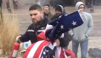 "A FedEx driver in Iowa City, Iowa, grabs ""Old Glory"" from flag-burning protesters on Thursday, Jan. 26, 2017. (Twitter, Stephen GruberMiller)"