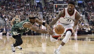 Toronto Raptors forward Terrence Ross (31) and Milwaukee Bucks guard Jason Terry (3) reach for the ball during the first half of an NBA basketball game in Toronto on Friday, Jan. 27, 2017. (Nathan Denette/The Canadian Press via AP)