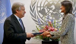 Former South Carolina Governor Nikki Haley, right, presents her credentials to United Nations Secretary General Antonio Guterres, left, as the new U.S. Ambassador to the United Nations, Friday Jan. 27, 2017 at U.N. headquarters. (AP Photo/Bebeto Matthews)