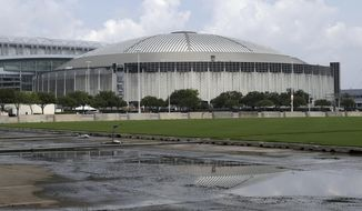 FILE - In this July 30, 2014, file photo, the Houston Astrodome is reflected in a puddle in Houston. The Texas Historical Commission voted Friday, Jan. 27, 2017, to grant landmark status to the no-longer-used enclosed stadium amid plans to redevelop the no-longer-used enclosed stadium. (AP Photo/Pat Sullivan, File)