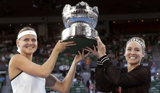 Bethanie Mattek-Sands, right, of the U.S. and Lucie Safarova of the Czech Republic hold their trophy aloft after defeating Andrea Hlavackova of the Czech Republic and Peng Shuai of China in the women's doubles final at the Australian Open tennis championships in Melbourne, Australia, Friday, Jan. 27, 2017. (AP Photo/Aaron Favila)