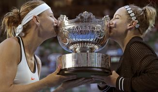 Bethanie Mattek-Sands, right, of the U.S. and Lucie Safarova of the Czech Republic kiss their trophy after defeating Andrea Hlavackova of the Czech Republic and Peng Shuai of China in the women's doubles final at the Australian Open tennis championships in Melbourne, Australia, Friday, Jan. 27, 2017. (AP Photo/Aaron Favila)
