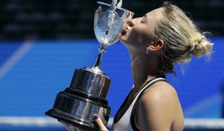 Ukraine's Marta Kostyuk kisses her trophy after defeating Switzerland's Rebeka Masarova in the girls singles final at the Australian Open tennis championships in Melbourne, Australia, Saturday, Jan. 28, 2017. (AP Photo/Aaron Favila)