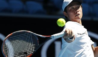 China's Wu Yibing plays a forehand return to Israel's Yshai Oliel during their junior boys' singles semifinal at the Australian Open tennis championships in Melbourne, Australia, Friday, Jan. 27, 2017. (AP Photo/Dita Alangkara)