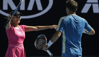 India's Sania Mirza, left, celebrates with Ivan Dodig of Croatia after winning their mixed doubles' semifinal against Australia's Samantha Stosur and Sam Groth at the Australian Open tennis championships in Melbourne, Australia, Friday, Jan. 27, 2017. (AP Photo/Aaron Favila)