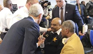 In this photo taken from video, Chicago Mayor Rahm Emanuel, left, hands a bottle of water to Police Superintendent Eddie Johnson after Johnson became wobbly during a news conference Friday, Jan. 27, 2017 in Chicago. The Chicago Sun-Times reports that there were requests for candy for Johnson as he fell ill. The news conference was halted as Johnson was attended to and an ambulance and a fire truck arrived. (Fran Spielman/Chicago Sun-Times via AP)