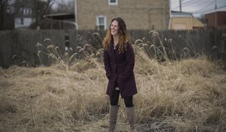 In this Thursday, Jan. 19, 2017 photo, Demi Kolke stands in the vacant lot she purchased in 2016 in Homewood, Pa.. The lot originally belonged to Kenneth Stubbs, a resident of Homewood who Kolke got to know through her work with Operation Better Block. In February, 2014, Stubbs was found murdered. Kolke is working to convert the lot into a community and cultural celebration space called Kenny's in honor of Stubbs. (Andrew Russell/Pittsburgh Tribune-Review via AP)