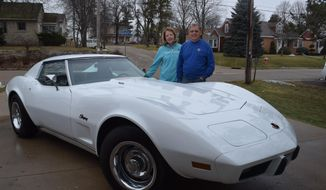 This Jan. 23, 2017 photo shows Wanda Udovich, left, and her husband, Rich Udovich, standing behind their Corvette in Watertown, Wis.   In 1988, Udovich lost a friend and ultimately became owner of that man's 1976 Corvette. This past Christmas, Udovich received what he thought was a Christmas card. The correspondence however, turned out to be a proposal from the vehicle's original owner to buy the car back. ( Steve Sharp/The Watertown Daily Times via AP)