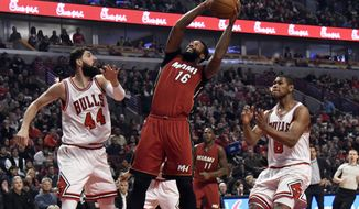 Miami Heat forward James Johnson (16) looks for a shot as Chicago Bulls forwards Nikola Mirotic (44) and Cristiano Felicio (6) defend during the first half of an NBA basketball game in Chicago, Friday, Jan. 27, 2017. (AP Photo/David Banks)