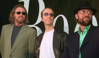 This July 29, 1998, file photo shows brothers Barry, Robin and Maurice Gibb, left to right, of the pop group the Bee Gees during a news conference in Miami Beach, Fla. The Recording Academy and CBS will pay tribute to the Bee Gees two days after the Grammys with a concert featuring a range of artists, including Celine Dion, Andra Day, John Legend and Keith Urban. The concert will be taped Feb. 14 at the Microsoft Theater, to be broadcast on CBS later this year. (AP Photo/Marta Lavandier, File)