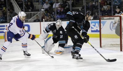 San Jose Sharks' Paul Martin (7) clears the puck after a shot which was deflected by goalie Martin Jones, center, as Edmonton Oilers' Zack Kassian (44) closes in during the second period of an NHL hockey game Thursday, Jan. 26, 2017, in San Jose, Calif. (AP Photo/Marcio Jose Sanchez)