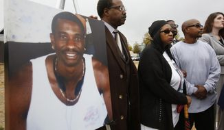 FILE - In this Oct. 3, 2016 file photo, a picture of Joseph Mann, who was killed by Sacramento Police last July, is displayed at a news conference held by his sister, Deborah, center, and brother, Robert Mann, right, in Sacramento, Calif. The Sacramento County District Attorney's Office on Friday, Jan. 27, 2017, cleared the two police officers involved, saying they acted lawfully when they shot and killed Mann. (AP Photo/Rich Pedroncelli, File)