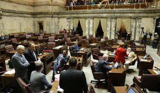 "Democrats confer on the Senate floor as the Republican side sits empty during a recess, Friday, Jan. 27, 2017, in Olympia, Wash. Senators were debating whether to vote on the ""levy cliff"" bill, which would delay a reduction in the amount of money school districts can collect though property taxes. (AP Photo/Ted S. Warren)"