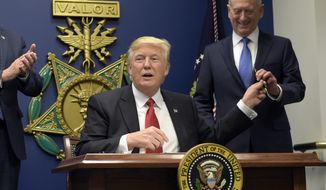 President Donald Trump, left, hands Defense Secretary James Mattis, right, a pen after he signed an executive action on rebuilding the military during an event at the Pentagon in Washington, Friday, Jan. 27, 2017. (AP Photo/Susan Walsh)
