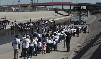 Hundreds of persons line up meet friends and relatives on the U.S. - Mexico border on the Rio Grande in Ciudad Juarez, Mexico, Saturday, Jan 28, 2017. Hundreds of people from Ciudad Juarez gathered along the U.S.-Mexico border to reunite with relatives from El Paso, Texas, for a few precious minutes. (AP Photo/Christian Torres)