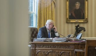 President Donald Trump speaks on the phone with Russian President Vladimir Putin, Saturday, Jan. 28, 2017, in the Oval Office at the White House in Washington. (AP Photo/Andrew Harnik)