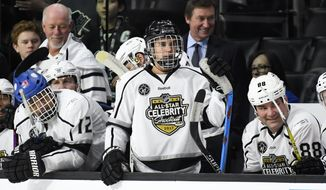 Celebrity players, from left, Cuba Gooding Jr., Justin Bieber and Eric Lindros sit on the bench as Team Gretzky head coach Wayne Gretzky, top center, stands in the background during the first period of the NHL All-Star Celebrity Shootout at Staples Center, Saturday, Jan. 28, 2017, in Los Angeles. The NHL All-Star Game is scheduled to be played at Staples Center on Sunday. (AP Photo/Mark J. Terrill)