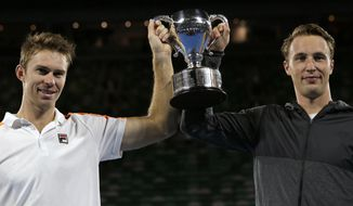 Finland's Henri Kontinen, right, and Australia's John Peers hold their trophy aloft after winning the men's doubles final against Bob and Mike Bryan of the U.S. at the Australian Open tennis championships in Melbourne, Australia, Saturday, Jan. 28, 2017. (AP Photo/Aaron Favila)