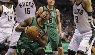 Boston Celtics' Isiah Thomas looks to put up a shot against Milwaukee Bucks Greg Monroe (15) and Matthew Dellavedova (8) during the second half of an NBA basketball game Saturday, Jan. 28, 2017, in Milwaukee. (AP Photo/Jeffrey Phelps)