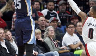 Memphis Grizzlies forward Chandler Parsons, left, shoots a 3-point basket over Portland Trail Blazers guard Damian Lillard during the second half of an NBA basketball game in Portland, Ore., Friday, Jan. 27, 2017. (AP Photo/Craig Mitchelldyer)