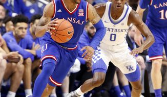 Kansas' Frank Mason III, left, looks for an opening on Kentucky's De'Aaron Fox (0) during the first half of an NCAA college basketball game, Saturday, Jan. 28, 2017, in Lexington, Ky. (AP Photo/James Crisp)